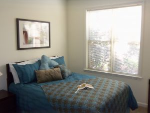 bed with blue linens and a closed window next to it.